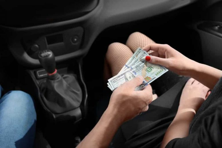 Young prostitute receiving money from client in car - Jacksonville criminal defense attorney